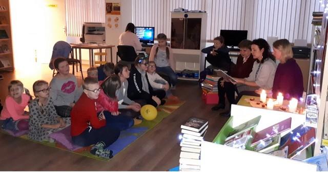 Bērni uz grīdas sasēdušies klausās kā viņiem lasa priekšā grāmatu.
