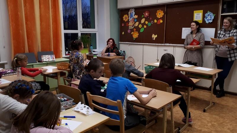 Bibliotekāres lasa. Bērni klausās un zīmē.