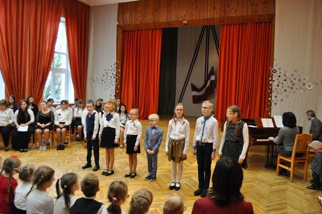 Skolēni nostājušies skatītāju priekšā un dzied.