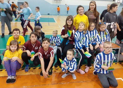 Bērni sporta zālē sēž pēc sacensībām.