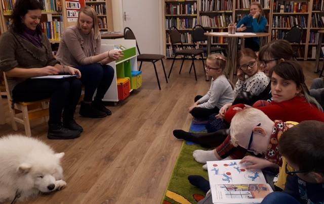 Pasākuma vadītājas lasa grāmatu, bērni sēž priekšā un arī lasa, suns guļ.