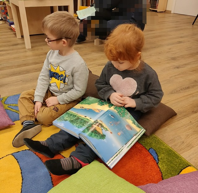 Bērni sēž uz grīdas un lasa grāmatu