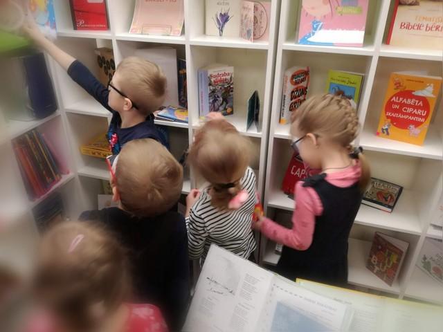Bērni pie grāmatu plaukta meklē grāmatas.