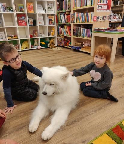 Bērni glauda lielu baltu suni.