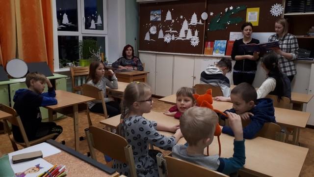 Bibliotekāres lasa grāmatu, bērni sēž solos un klausās