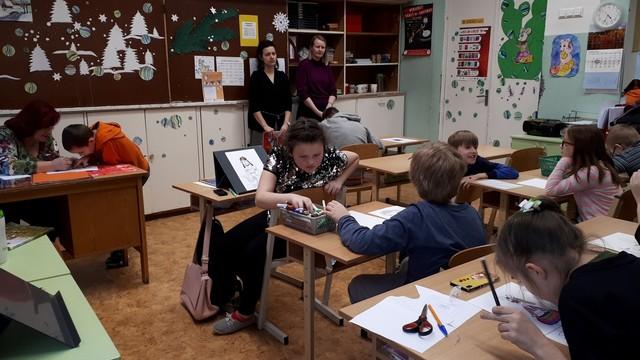 Skolēni aktīvi zīmē, skolotāja palīdz.