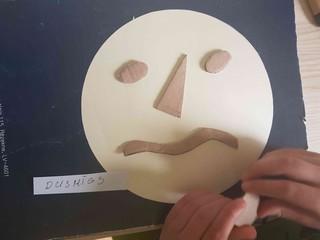 Albets no kartona veido dusmīgu seju.