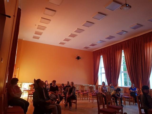 Operas skatītāji skolas aktu zālē, ievērojot distanci.