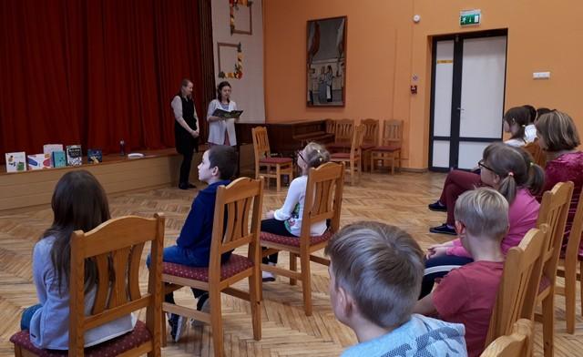 Skolēni aktu zālē klausās pasākuma vadītāju grāmatu lasījumu.