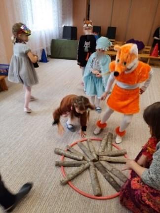Bērni maskās veido apli ar koka gabaliņiem vērsu uz tā centru
