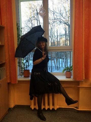 Skolātja Ligita ar lietussargu pie loga.
