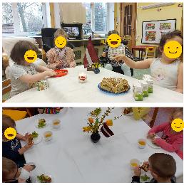 Bērni sēž pie galda un mielojas ar gardumiem.