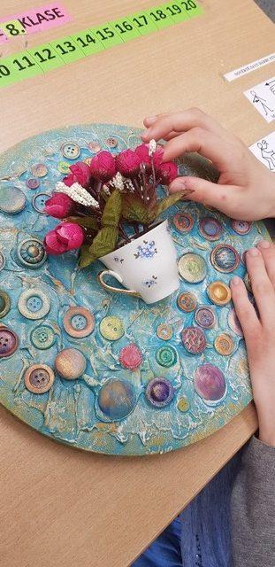Mākslas darbs - krūzīte ar ziediem uz apļa ar pogām.