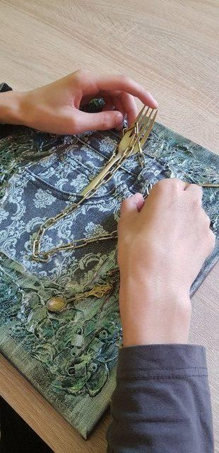 Mākslas darbs - uz kvadrātveidīgas pamatnes dakšiņa un metāla stieplītes.