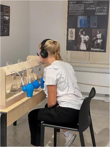 Meitene pie galda ar zilām kolbām.