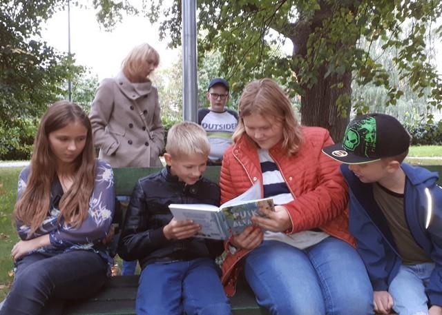 Bērni pēta un lasa grāmatu