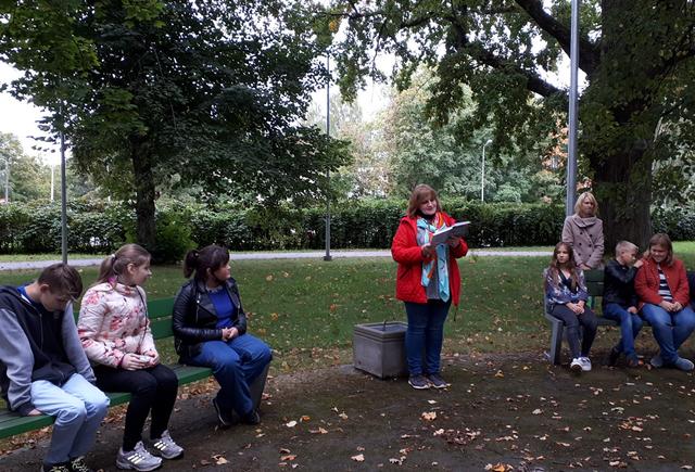 Skolotāja parkā, bērniem lasa grāmatu